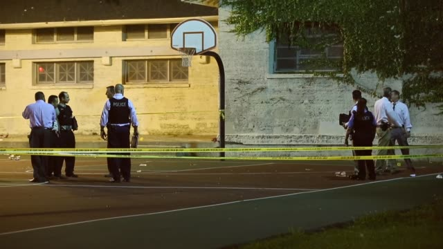 Long Shot Police investigate the scene in Cornell Square Park in the Back of the Yards neighbourhood on the Southside where 13 people including a...