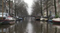 Long Shot push-in - Boats dock along a waterfront neighborhood in Amsterdam. / Amsterdam, Netherlands