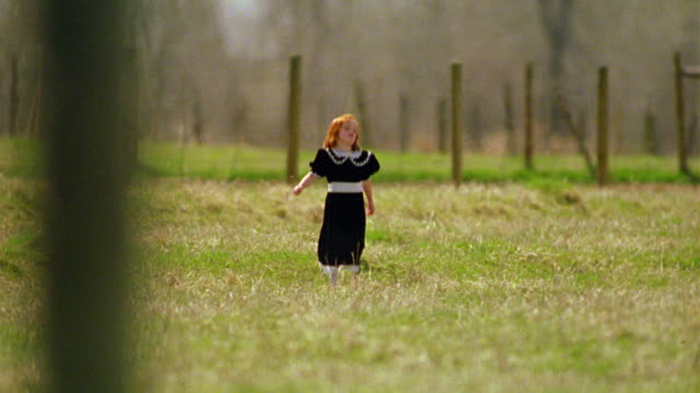 long shot redheaded girl in black dress skipping + running in green field toward camera / fence in background