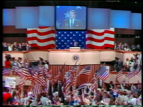 1984 long shot Ronald Reagan standing at podium on big screen above / people waving US flags in foreground