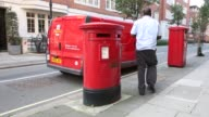Long Shot Royal Mail employee collecting letter from a mail box