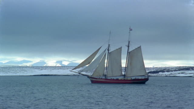 Long shot ship sailing in water / snow-covered coastline and mountains in background / Arctic
