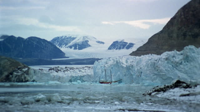 Long shot ship sailing past glacier / snow-covered mountains in background / Arctic