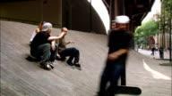 Long shot skateboarders talking on ramp at Brooklyn Banks / man skating past and giving high five / NYC