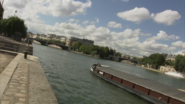 Long Shot static - A barge floats on the Seine River in Paris. / Paris, France