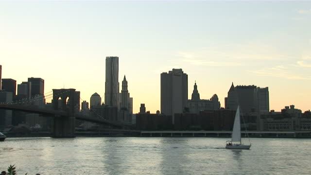 Long Shot  static - A sailboat sails along a river past New York City. /  New York City, New York, USA