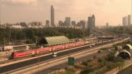 Long Shot static - Heavy traffic streams past a train toward downtown Tel Aviv. / Tel Aviv, Israel