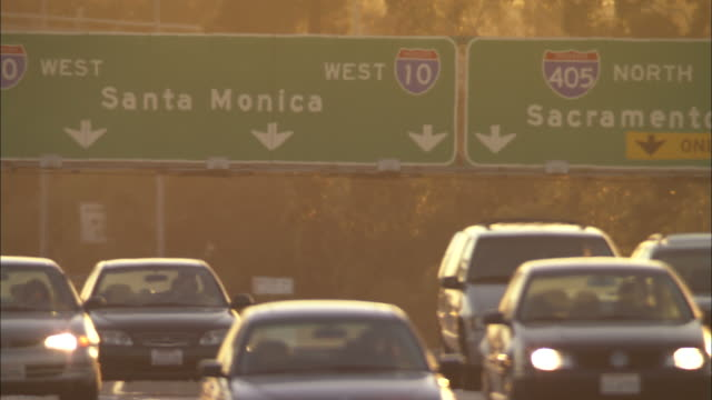 Long Shot static - Route and destination signs above a freeway are obscured in smog/Los Angeles, California, USA