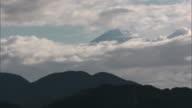 Long shot: Summit of Mt. Fuji visible amid a gap in the clouds, Shizuoka, Japan