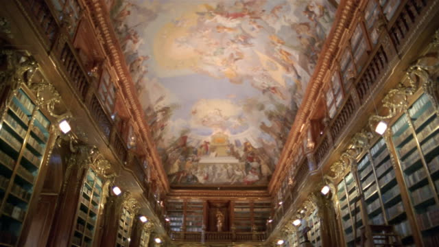 Long shot tilt down from fresco on roof to stacks in Philosophical Hall in library at Strahov Monastery / Prague