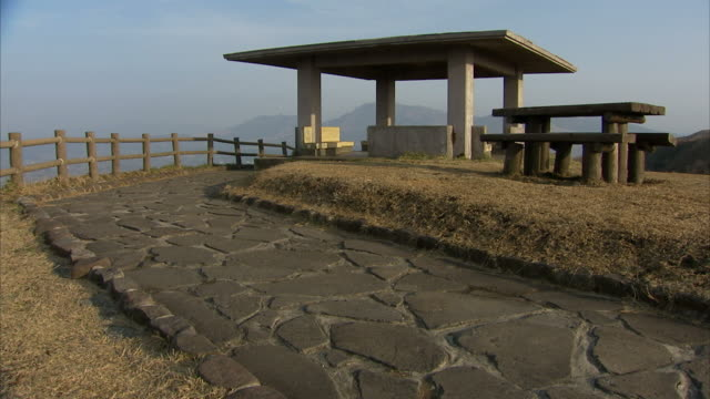 Long Shot tilt-up - A pavilion and picnic table creates a scenic overlook. / Kumamoto, Japan