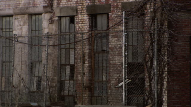 Long Shot tilt-up - Chain-link fencing surrounds an old, dilapidated factory. / Connecticut, USA