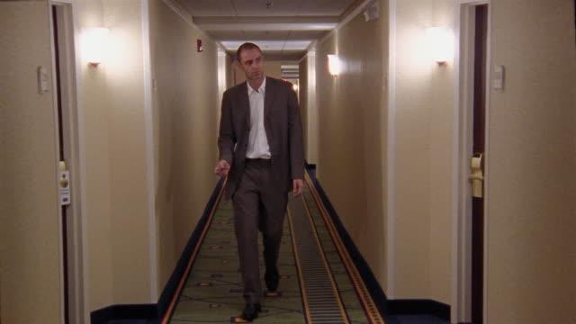 Long shot tracking shot man walking down hotel hallway / going into room / tracking shot empty hallway