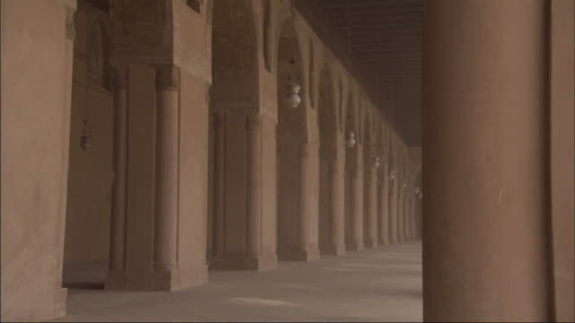 Long Shot, tracking-left - Lamps sway between columns at the Mosque of Ibn Tulun / Egypt