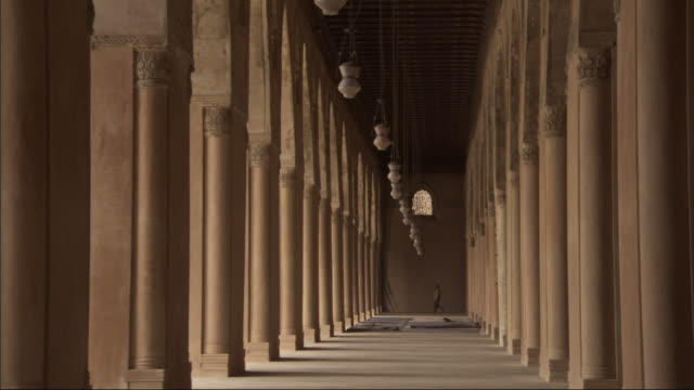 Long Shot, tracking-right - Lamps sway between columns at the Mosque of Ibn Tulun / Egypt