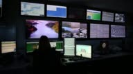 Long shot US Border Patrol agents at the Buffalo sector headquarters monitor video feeds from cameras placed along the USCanada border The video...