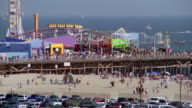 Long shot view of crowds on Santa Monica Pier and beach / Pacific Ocean in background / Santa Monica, California