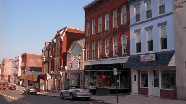 Long shot view of storefronts and light traffic along main street in small town