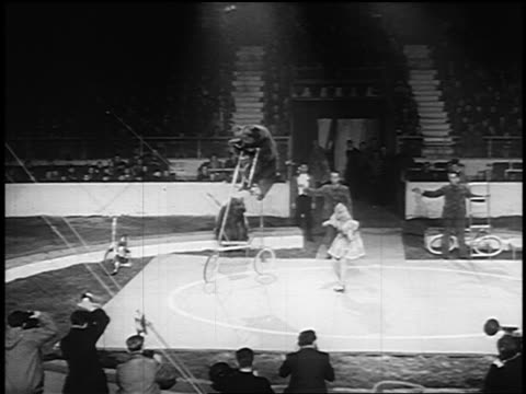 B/W 1955 long shot woman guiding bear riding very tall bicycle in circus