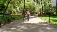 Long shot young couple walking in Central Park / man pointing to something off CAM / New York City