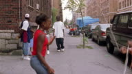 Long shot young man walking down street and greeting friend / girls jumping rope (double dutch) in foreground