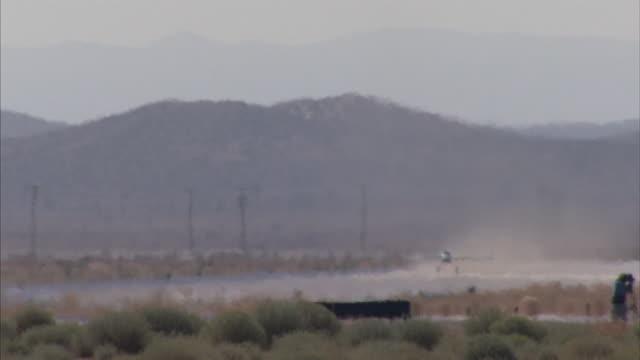 Long Shot_pan-left tilt-up - A rocket plane lifts off from a runway.
