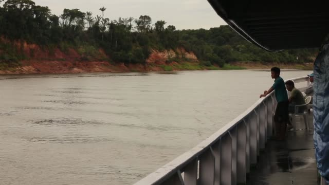 Long Tracking Shot men are watching the changing landscape from a riverboat moving across the Amazon A transport riverboat travels in the Brazilian...