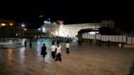 Long view of the Wailing Wall and Temple Mount with the Dome of the Rock in the background with people walking in at night
