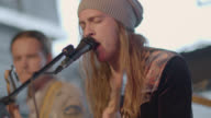 Long-haired guitarist sings into microphone with band at live music showcase