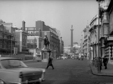 Longshot of Whitehall with the equestrian statue of Charles I and Nelsons Column visible in the distance The camera pans left over pedestrians and...