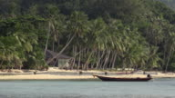 Longtail boat and palm trees at sandy beach