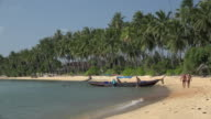 Longtail boat and tourists at beach with palm trees