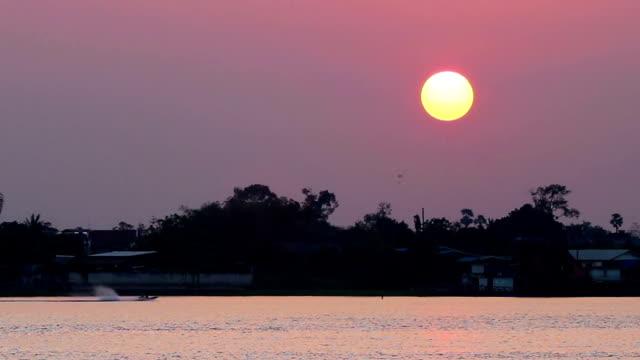 Longtail-båt i floden vid vackra solnedgången
