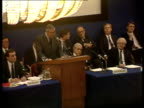 Rowland suing for damages London LTMS Sir Edward Du Cann standing speaking at podium at shareholders meeting PULL TGV Shareholders sitting at meeting...