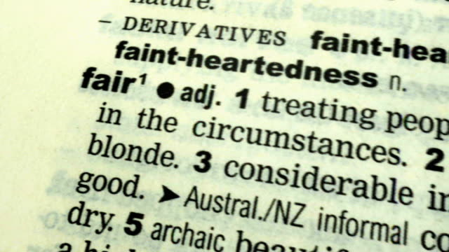 A look at fairness in politics and business ENGLAND London INT Setup shots of open dictionary on table and close shot of definition of word 'fair'