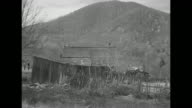 Looking down hillside at shack with Blue Ridge Mountains in bg / shack with mountain behind it / MS longtime mountaineer William Dodson with beard...