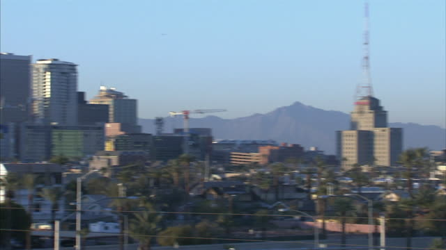 QUICK PAN From Westward Ho building pass downtown Phoenix skyline cityscape highrises skyscrapers buildings vehicles trucks moving on highway lower...