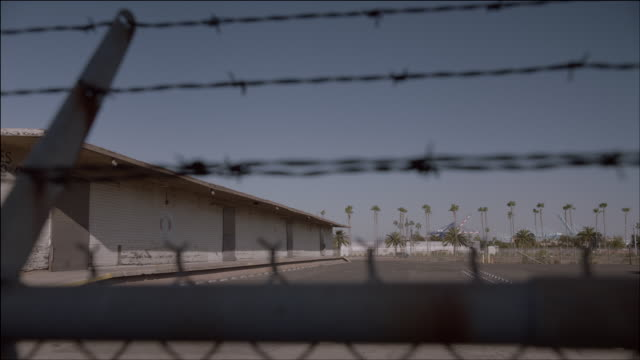 WS Looking through a barbed wire fence at a building with palm trees and traffic in the background