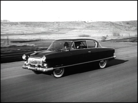 / MS looking through front windshield of man driving 1953 Nash Ambassador slow dolly out / WS couple sitting in their Nash parked in front of 1950s...