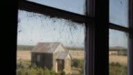 Looking through the window: a small church in a farm and a spider web, Victoria. Australia