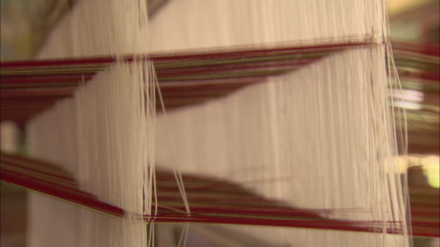 A loom weaves silk threads.