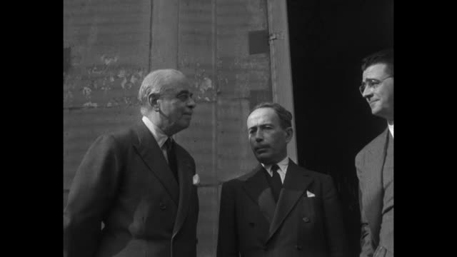Lord Hastings Ismay and French Prime Minister Antoine Pinay with another man wearing glasses and holding cigarette at entrance of Palais de Chaillot...