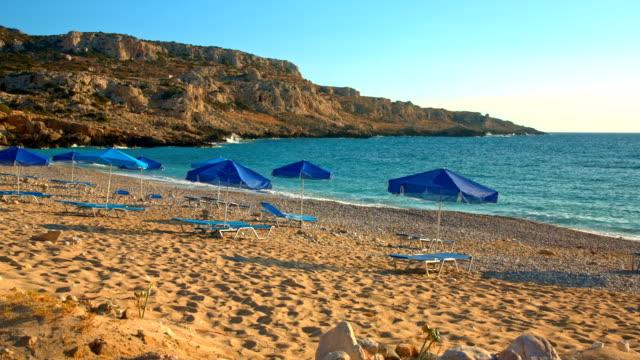 Lounge stoelen en parasols aan strand Potali op eiland Karpathos
