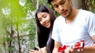Love couple playing guitar in nature.