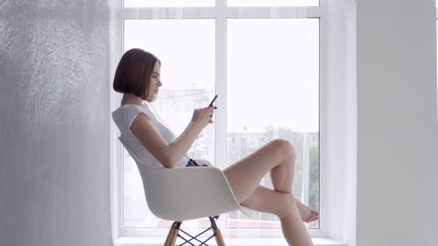 Lovely girl enjoying rest and sitting on armchair