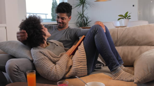 Loving African American couple reading a book while relaxing on the sofa at home.