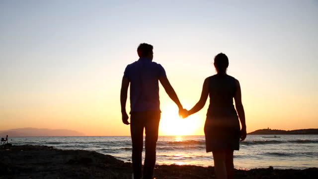 Loving couple embracing on the beach at sunset