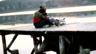 A loving couple in a warm hug on a dock with a baby dog