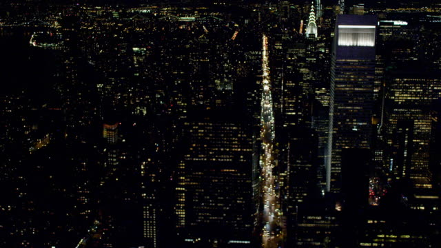 Low Altitude WS Cityscape Midtown to Lower East Side passing busy traffic north south avenues Chrysler Building midblock over 3rd 2nd 1st Avenues to...