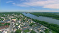 Low altitude forward POV aerial over New Cumberland, PA and the Susquehanna River with the skyline of Harrisburg, PA in BG